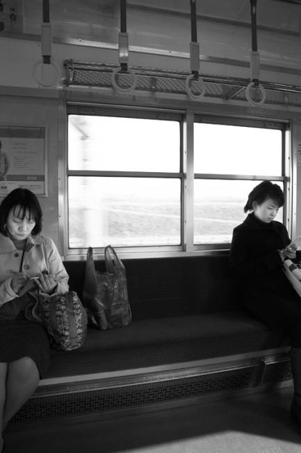 Two women on the train to Dazaifu, Japan. One reading a book, one reading mobile phone.