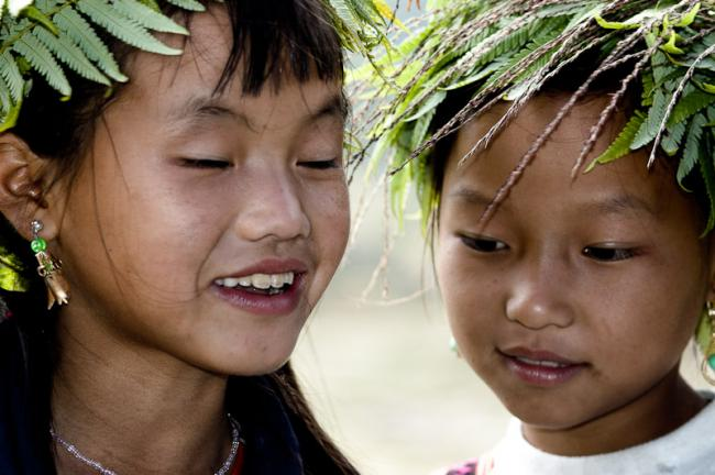 Two Black Hmong girls with fern in their hair. Sapa, Vietnam.
