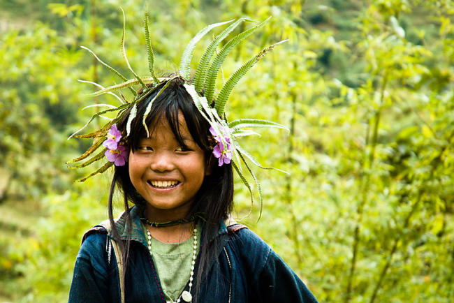 Smiling Black Hmong girl in front of lush bamboo. Sapa, Vietnam