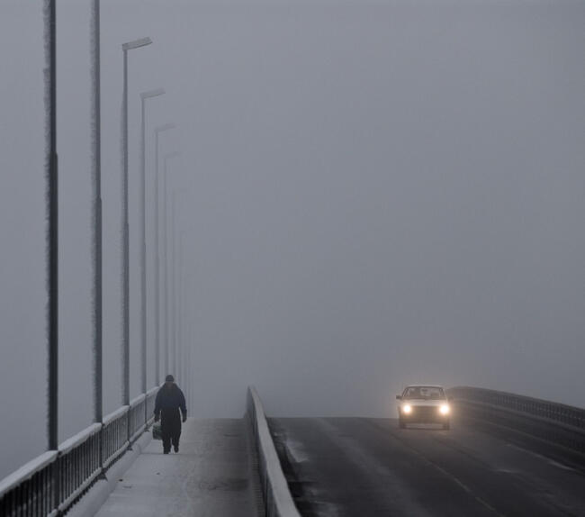 A man walking on a bridge during winter