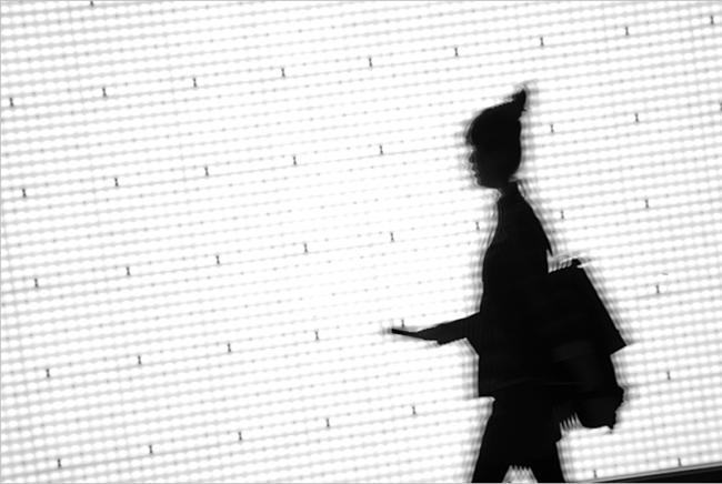 Silhouette of woman passing by bright screen