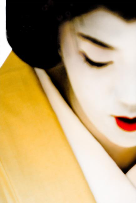 Portrait of a geisha in yellow kimono and red lipstick