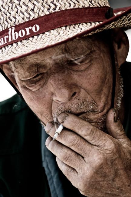 Korean man with Marlboro hat smoking a cigarette